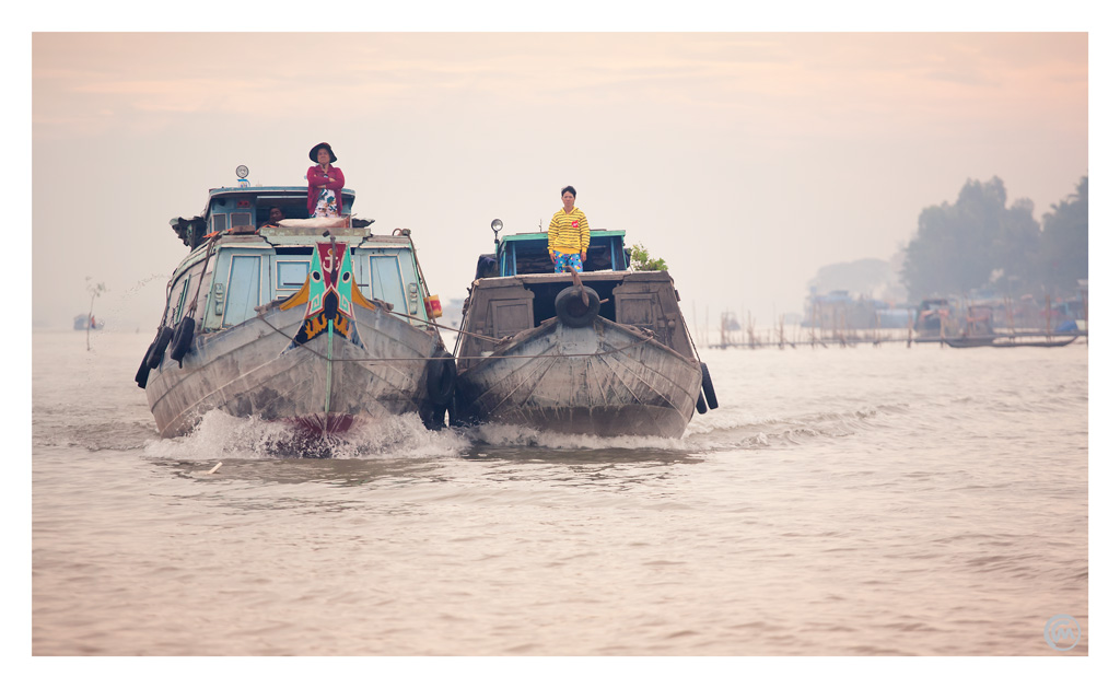 House boats on the move at dawn on the Mekong River, Vietnam