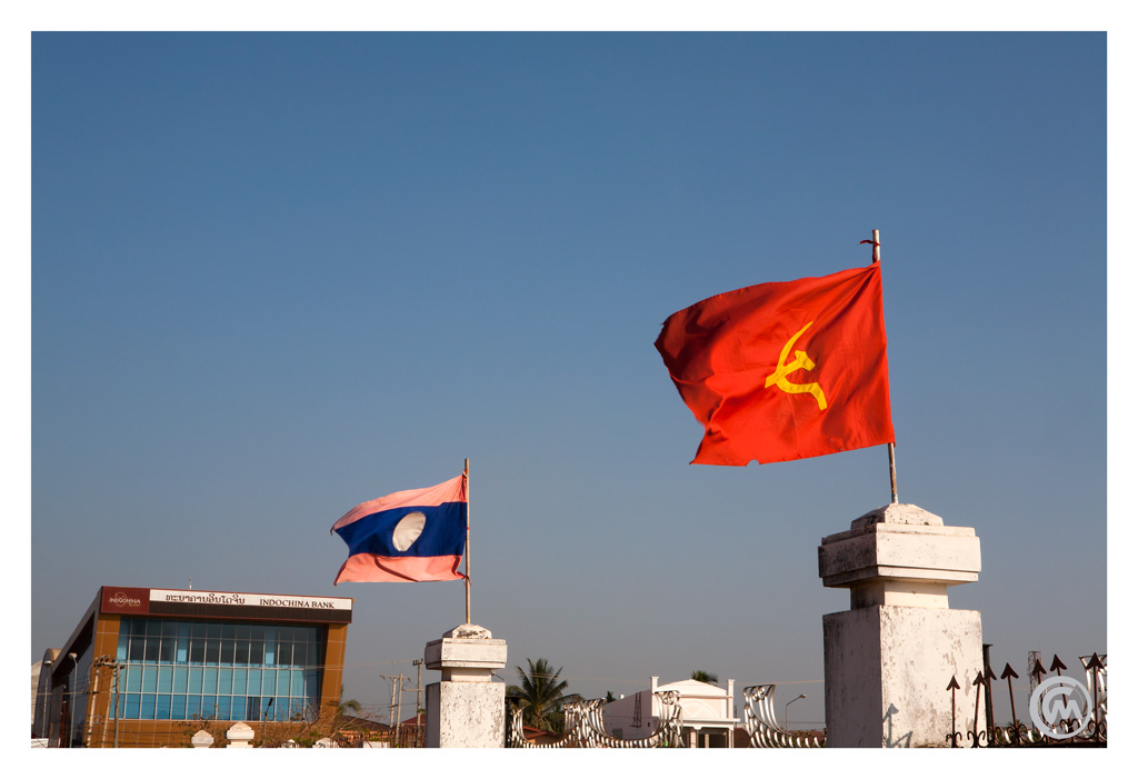 Laos and communist flags in from of the Indochina Bank in Pakse, Laos