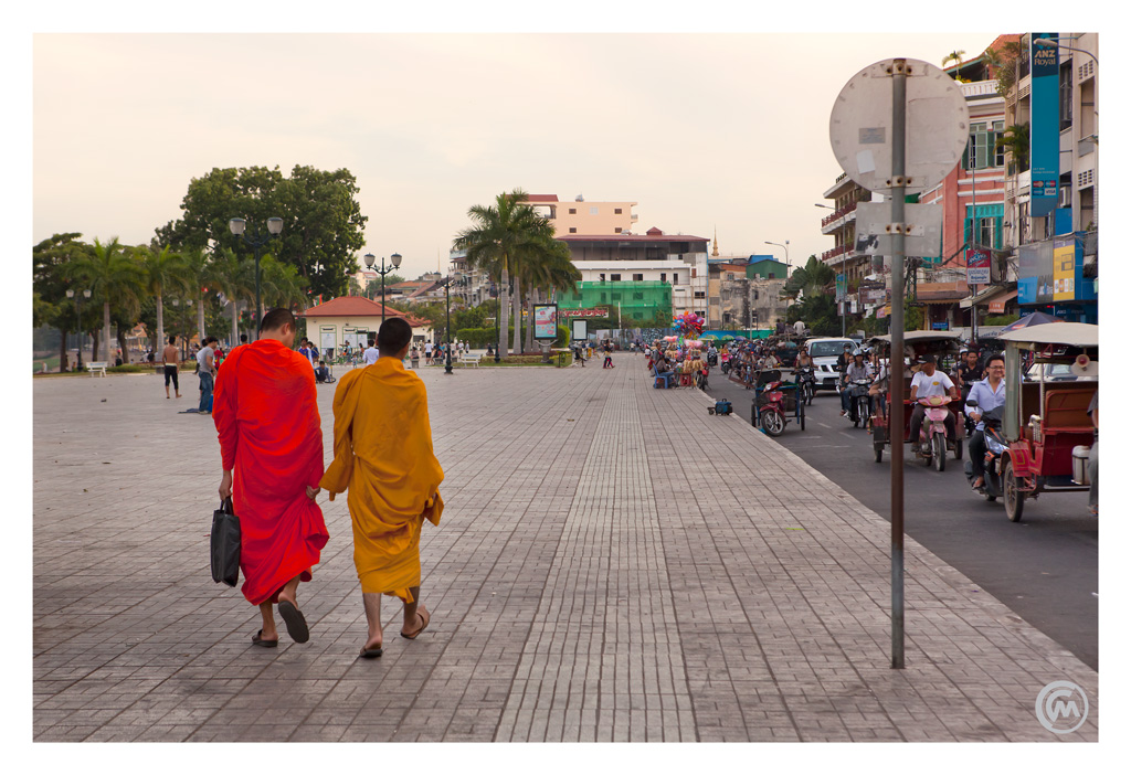 Two monks walk Sisowath Quay in Phnom Penh, Cambodia